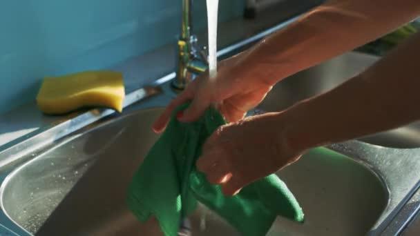 Vértes hölgy kezét mossa zöld rag víz Jet csap felett rozsdamentes acél mosogató, modern konyha