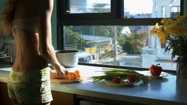 zadní pohled krásné sportovní dívka kusy velké žluté papriky s nožem v moderní kuchyni