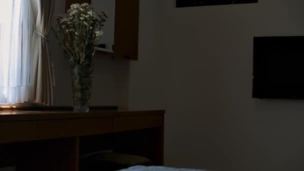 zadní pohled štíhlá blondýnka v šortkách a vrchol přichází na Bílé květiny ve váze na okenní parapet a uspořádá kytice