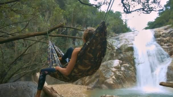 Detailní záběr zadní pohled dívka obrázek uvolňuje leží v houpací síti vazby mezi stromy proti obrazové vodopád