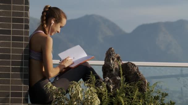 Großansicht Seite Ansicht Mädchen Kopfhörer scrollt durch Tagebuchseiten Notizen auf Dach gegen fernen Hügel