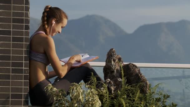 blondýnce s COP v sluchátka zavře papír deníku má šálek kávy na střeše proti obrazové hills