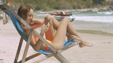 side view attractive young lady with smartphone sits in blue wooden beach chair on sunny coast