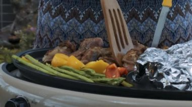 closeup person turns over tasty pork ribs with spatula and knife on electric grill against woman blue and grey dress