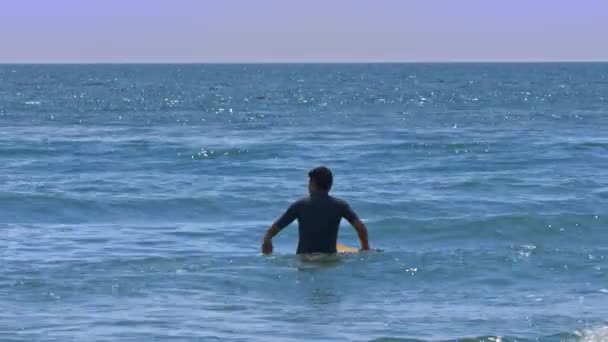 backside view guy in surf suit goes into calm azure ocean holding yellow board waiting for wave