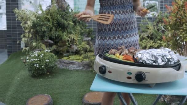 krásná štíhlá žena v šedém obrací Smažené maso a zeleninu špachtlí na grilu proti velkých květináčích na střeše