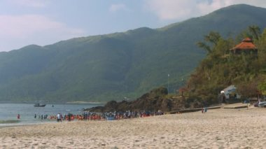 educators spend leisure time with kids from kindergarten on seashore against impressive hilly landscape