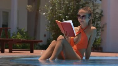 closeup delightful girl sits in swimming pool and reads interesting book on hotel resort territory