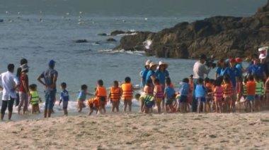 NHA TRANG/VIETNAM - MARCH 17 2018: Cute children from kindergarten gambol on ocean sand beach under educators supervision against beautiful rocks on March 17 in Nha Trang