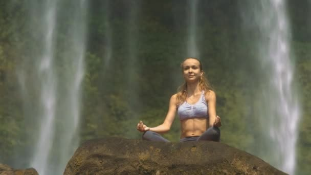 view from below pretty blonde girl does breathing exercise on stone against beautiful waterfall