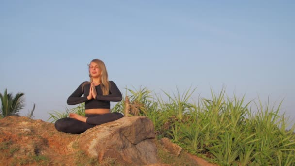 Dame im Trainingsanzug sitzt in Yoga-Pose auf grauer Felswand