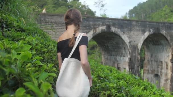 pretty girl in black t-shirt walks along green plantation