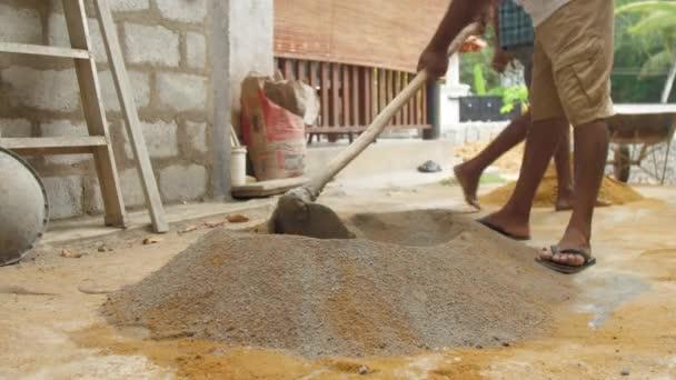 helyi építőmunkás keveri cement és homok közeli