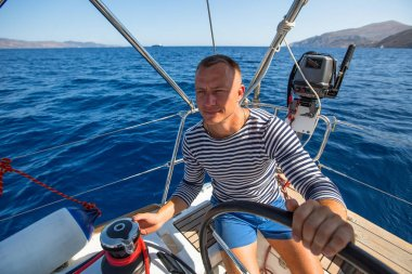 man at the helm of his yacht