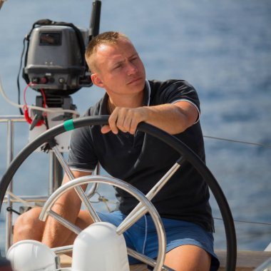 Man sits at the helm on the boat