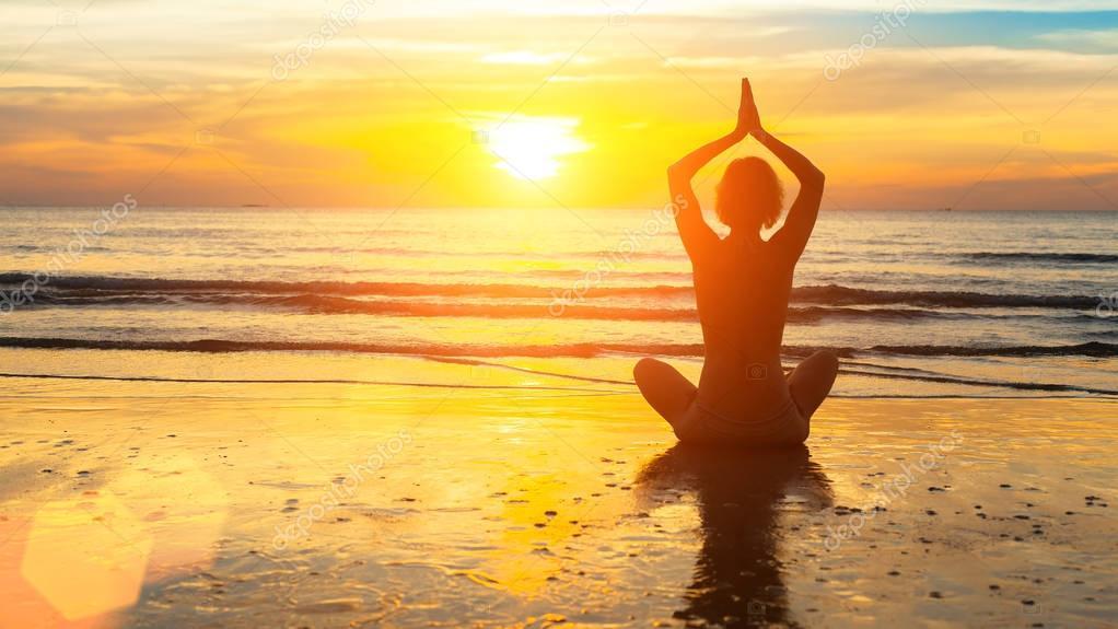 Silhouette woman yoga on the sea beach