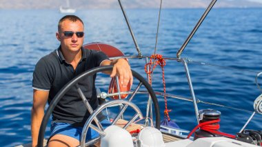 Man at the helm on the sailing boat