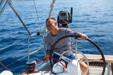Young man at the helm of sail boat
