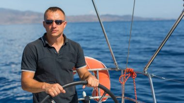 Man at helm on sailing boat