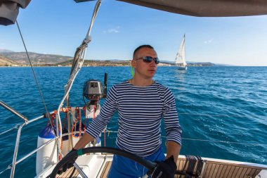 Skipper at helm of yacht