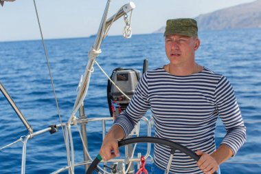 Young man skippering at helm