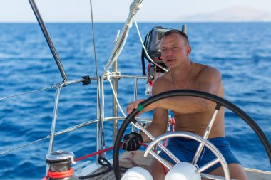 man controls sailing boat