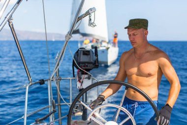 Man at helm of sail boat
