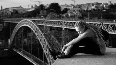 woman sitting against  Dom Luis I bridge