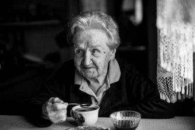 Elderly woman drinking tea, black and white portrait.