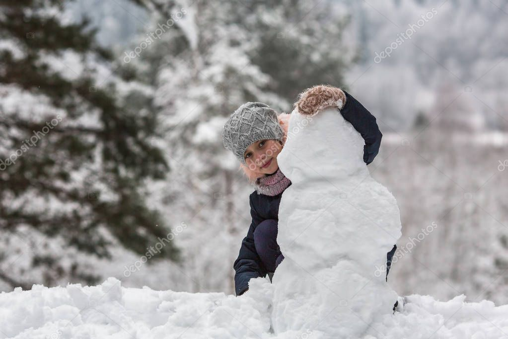 Little cute girl sculpts snowman in the winter Park.