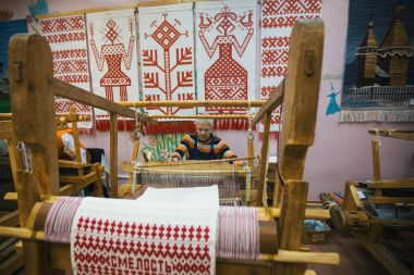 VAZHINY, LENINGRAD REGION, RUSSIA - DEC 21, 2017: Weaver while working in the Textile Studio of decorative art