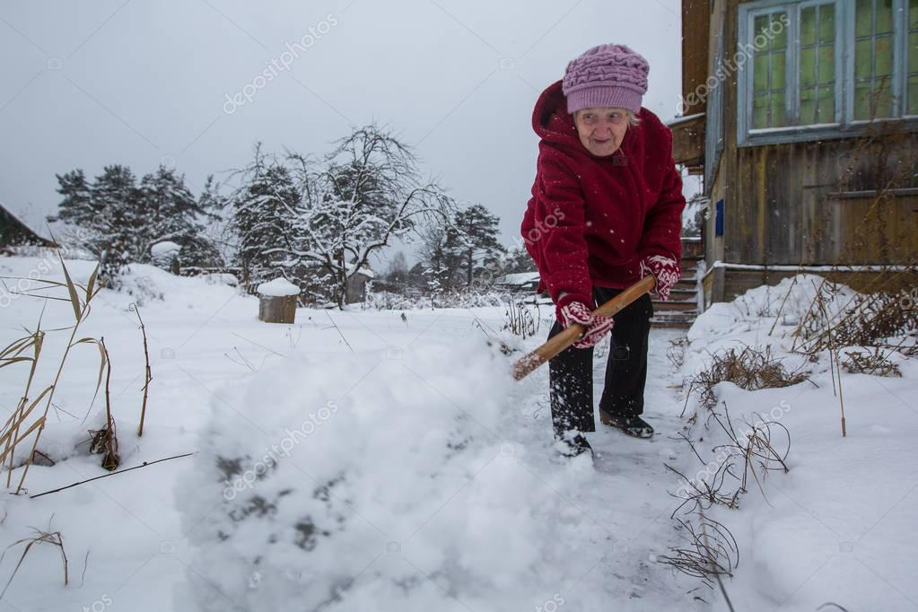 elderly woman cleans snow near his home in the village.