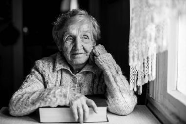 elderly woman with a book in hand sitting at a table near the window.
