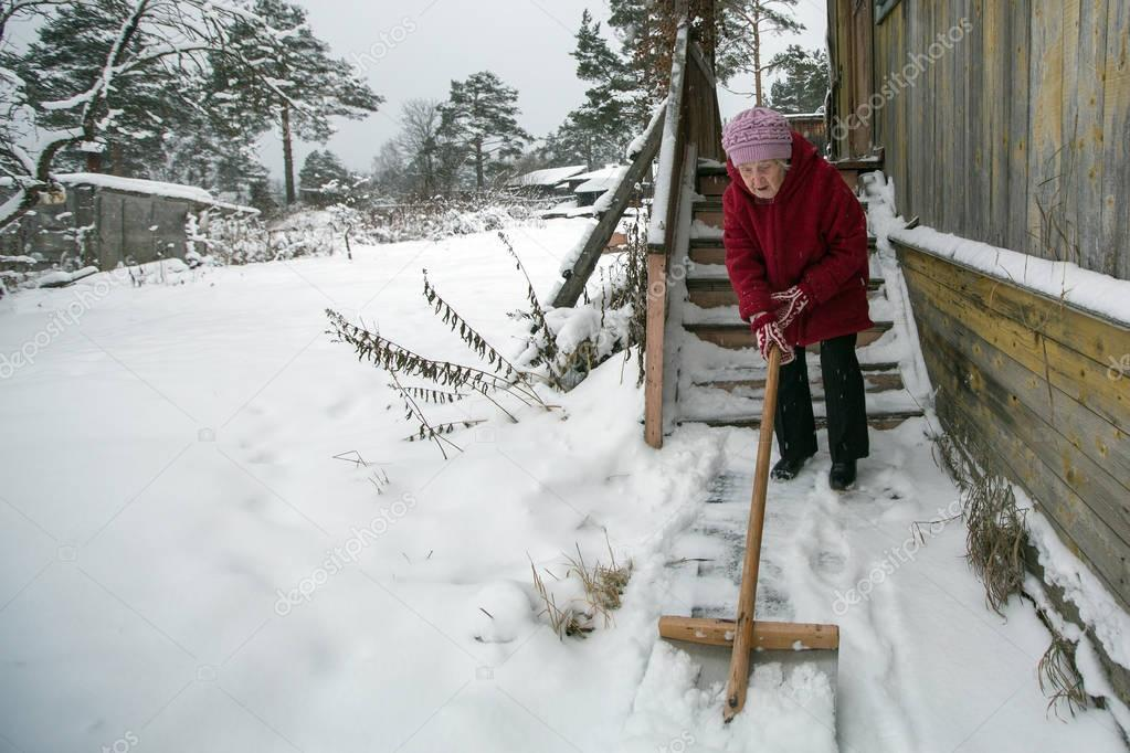 elderly woman cleans the snow shovel near his home in the village.