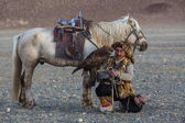 Sagsay, Mongólia - Sep 28, 2017: Kazah sas Hunter (Berkutchi) ló, egy szirti sas, a nyúl, a karját, a hegyekben Bayan-Olgii ajmag vadászat közben