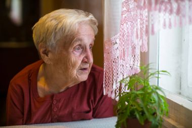 Older woman with longing looks out the window.