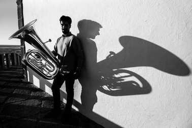 Young man play Tuba near the white wall the shadow of the tool. Black and white photo.