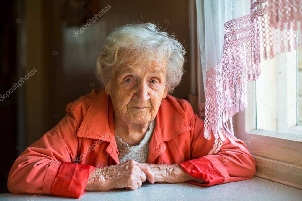Portrait of  elderly woman sitting in the cloak at the table.