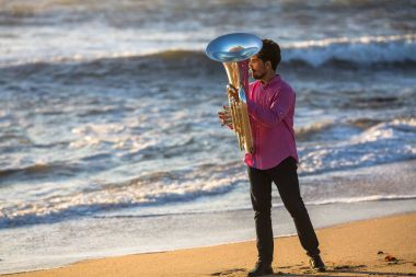 Man play the trumpet on Ocean coast during surf.