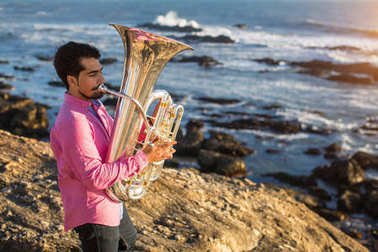 Young man play the trumpet on rocky sea coast during surf.