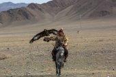 Olgiy, Mongólia - Sep 30, 2017: Sas vadász, hagyományos ruházat, egy szirti sas, a karján, a ragadozó madarak Berkutchi a Nyugat-mongóliai éves nemzeti verseny alatt: