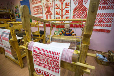VAZHINY, RUSSIA - DEC 21, 2017: Weaver while working in the Textile Studio of decorative art (Tekstilnaya Plastika) at municipal budgetary institution of culture.