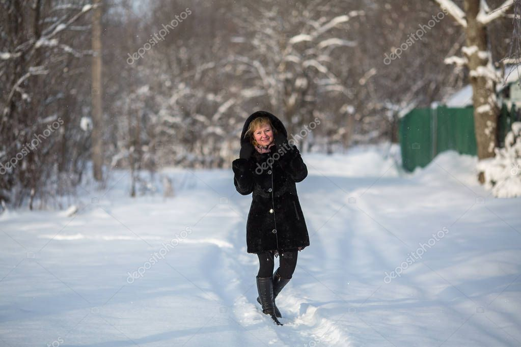Full-length portrait of a young woman in snowy weather outdoor.