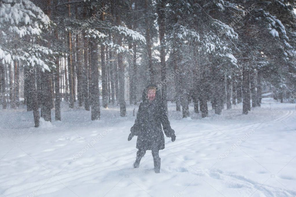 Young woman in the forest in a strong snowstorm.