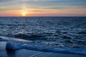 Nábřeží příboj oceánu během úžasný západ slunce