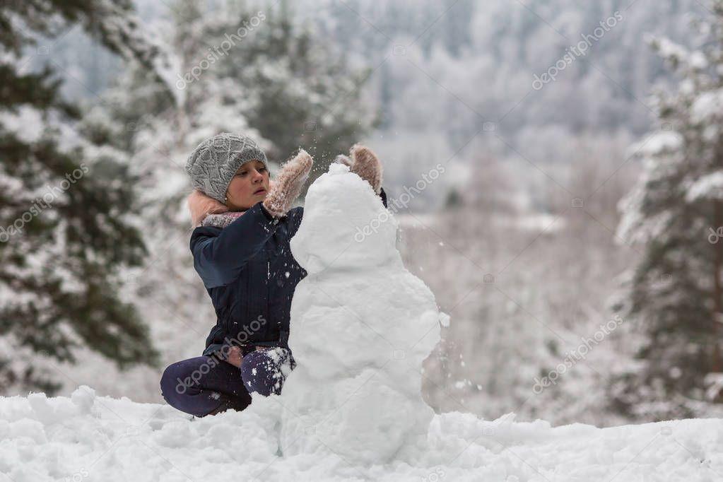 Little girl sculpts snowman in winter snowy Park.