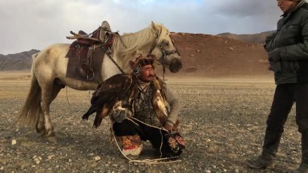 Sagsay, Mongolsko - září 28, 2017: Kazašské Eagle Hunter (Berkutchi) s koněm lov na zajíce s golden eagles v horách Bayan-Olgii ajmagu