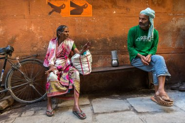 VARANASI, INDIA - MAR 26, 2018: Locals on one of the streets of the ancient city. According to legends, the city was founded by God Shiva about 5000 years ago.