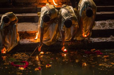 VARANASI, INDIA - MAR 17, 2018: Presenting flowers and candles to holy Ganges river. According to legends, the city was founded by God Shiva about 5000 years ago.