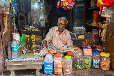 VARANASI, INDIA - MAR 26, 2018: Street seller in his small shop. According to legends, the city was founded by God Shiva about 5000 years ago.
